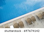 empty pool with sun loungers | Shutterstock . vector #697674142