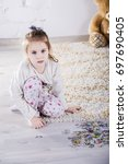 little girl  to collect a puzzle | Shutterstock . vector #697690405