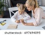 mother helping cute little... | Shutterstock . vector #697694095