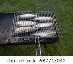 a fish. grilled on charcoal. in ... | Shutterstock . vector #697717042