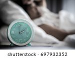 Small photo of Sleep changes and disorders or insomnia in elderly concept.Alarm clock time at 2 a.m. morning with blurry women lay down awake.