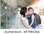 mother kissing schoolgirl in... | Shutterstock . vector #697981366