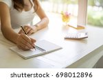 young woman writing on notebook ... | Shutterstock . vector #698012896