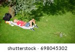 BRATISLAVA, SLOVAKIA - August 12, 2017: A man resting on a lawn in a park lying on a towel near a shade of wood to protect him from the sun burning rays - stock photo
