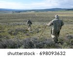 Two Hunters With Rifles Slung...