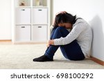 Small photo of people, grief and domestic violence concept - unhappy woman sitting on floor and crying at home
