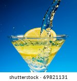 Glass with juice and lemon on the blue background - stock photo