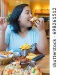 fat asian woman bite pizza at... | Shutterstock . vector #698261512