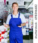 Small photo of positive man in uniform standing ready to help in tool-ware hypermarket
