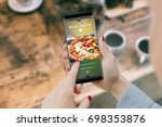 Small photo of Girl ordering pizza with smartphone, while drinking coffee. Online order food concept