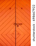 Small photo of Vertical image of a rustic wood door painted orange / red. It has diagonal lines, and a bolt. Slight vignetting in corners. Freeport, Bahamas. Accommodates text. Glad to alter it to fit your needs.