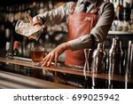 Stock photo barman in bar interior making alcohol cocktail professional bartender pours drink with a strainer 699025942