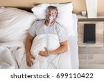 Small photo of Young Man Lying On Bed With Sleeping Apnea And CPAP Machine