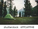 a green tent in the woods in... | Shutterstock . vector #699169948