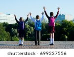 Small photo of Three schoolchildren amicably walking in the park, and raise their hands upwards