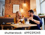 Stock photo couple of young people drinking coffee and eating cake in a stylish modern cafeteria 699239245