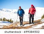 climbers walk through the snow... | Shutterstock . vector #699384502