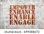 Small photo of empower, engage, enable, and enhance inspirational leadership concept - graffiti sign on stucco wall