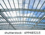 Steel structure roof truss under the construction building in the factory with blue sky - stock photo