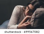 sad young woman with glasses... | Shutterstock . vector #699567082