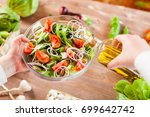 man pouring olive oil into...   Shutterstock . vector #699642742