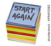 Small photo of start again motivational reminder - handwriting in black ink on an isolated stack of sticky notes