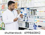pharmacist looking at shampoo... | Shutterstock . vector #699860842