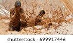 mud race runners  jump into... | Shutterstock . vector #699917446