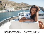 beautiful young woman on yacht. ... | Shutterstock . vector #699943312