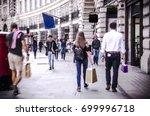 anonymous shoppers walking down ... | Shutterstock . vector #699996718