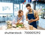 smiling young florists in... | Shutterstock . vector #700005292