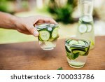 holding a glass with infused... | Shutterstock . vector #700033786