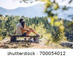 couple on mountain peak | Shutterstock . vector #700054012