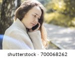 sad girl speaks on the phone in ... | Shutterstock . vector #700068262