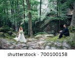 groom sits before a bride in... | Shutterstock . vector #700100158