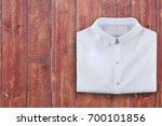 folded white shirt on brown... | Shutterstock . vector #700101856