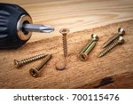 Small photo of Screw being screwed into a piece of wood by cordless drill. Concept tools and repair work.