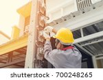 electrician in a gray uniform... | Shutterstock . vector #700248265