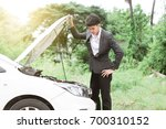 Small photo of Young stressed businessman having trouble with his broken car looking in frustration at failed engine.