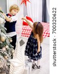 Small photo of Little brother and sister decorates a Christmas tree in the room. Concept winter, lifestyle, Merry Christmas.
