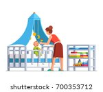 mother playing rattle to little ... | Shutterstock .eps vector #700353712