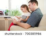 father with daughter at home | Shutterstock . vector #700385986