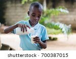 a child standing outside pours... | Shutterstock . vector #700387015