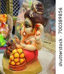 Small photo of Indian Hindu God Little Lord Ganesha Statue. ade of clay and coated with ceramic colors, handmade artistic effects, Beautiful artifacts