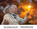 elderly couple in autumnal... | Shutterstock . vector #700396342