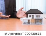 businessman holding a toy house ... | Shutterstock . vector #700420618