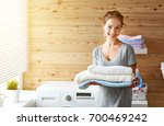 Stock photo a happy housewife woman in laundry room with washing machine 700469242