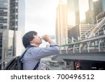 young asian man drinking a... | Shutterstock . vector #700496512