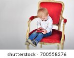 the boy is sitting on the red... | Shutterstock . vector #700558276