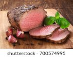 baked meat  garlic and basil on ... | Shutterstock . vector #700574995